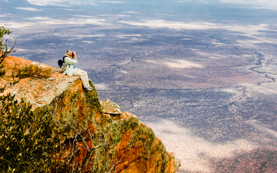 Person sits on cliff looking out at Kenya with binoculars