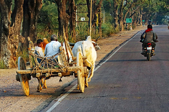 A hand-made wagon carries a family