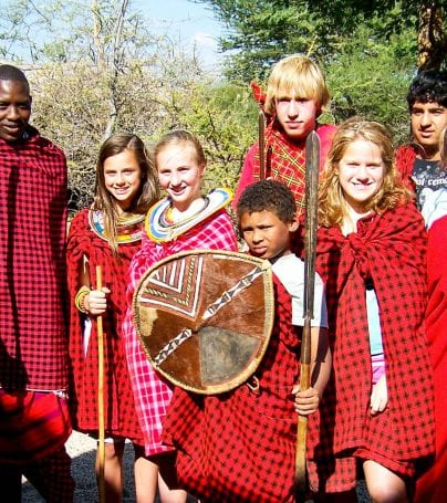 Travelers stand with Hadzabe group in Tanzania