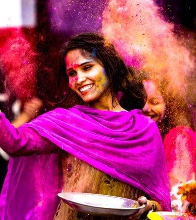 Woman dances at Holi Festival with colorful dust