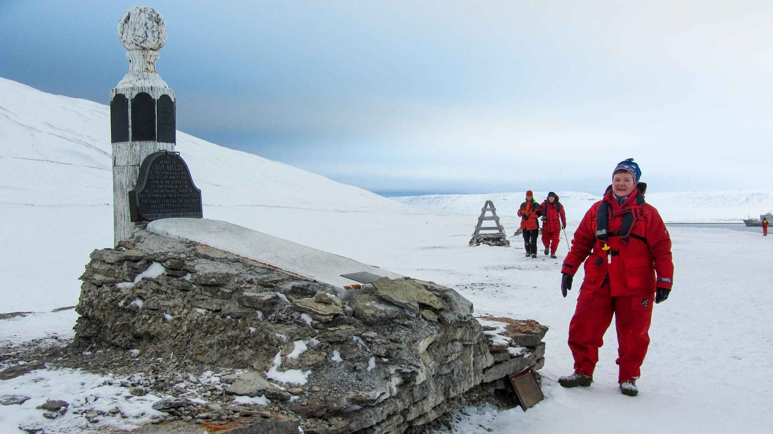 Woman stands next to monument in the Arctic