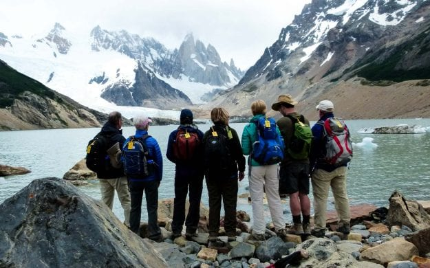 Argentina hiking group stands in front of mountain lake