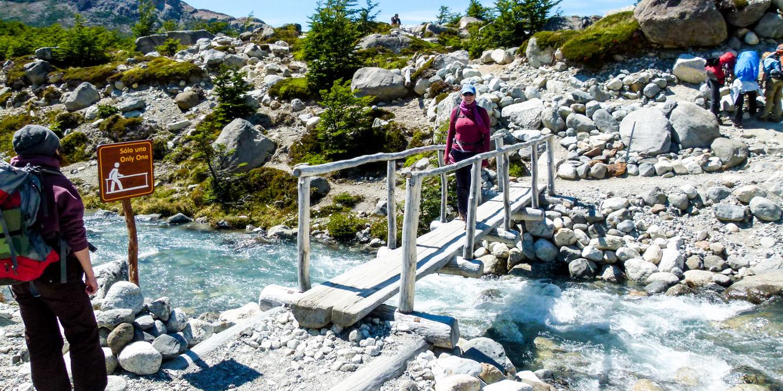 Hiking group crosses wooden bridge in Argentina