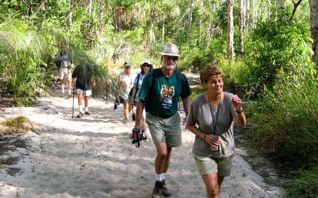 Travel group hikes in Australia forest