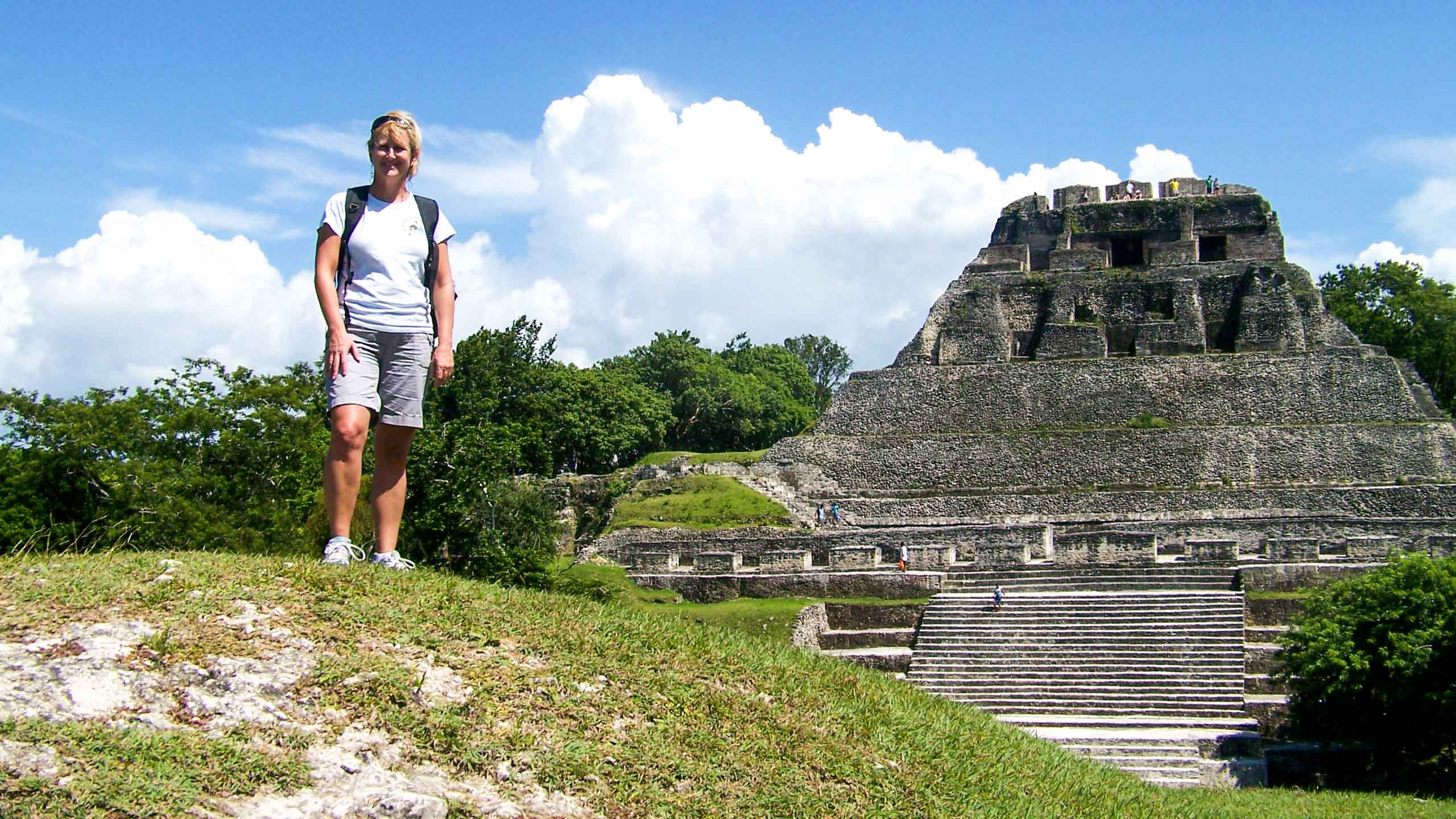 Woman stands on hill near Mayan temple in Belize
