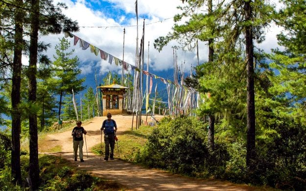 Hikers in Bhutan forest walk beneath colorful flags