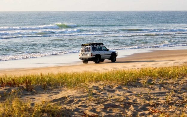 Car driving down beach of Fraser Island, Australia