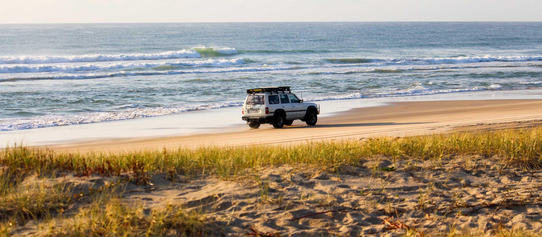 Car driving down beach of Fraser Island, Australia