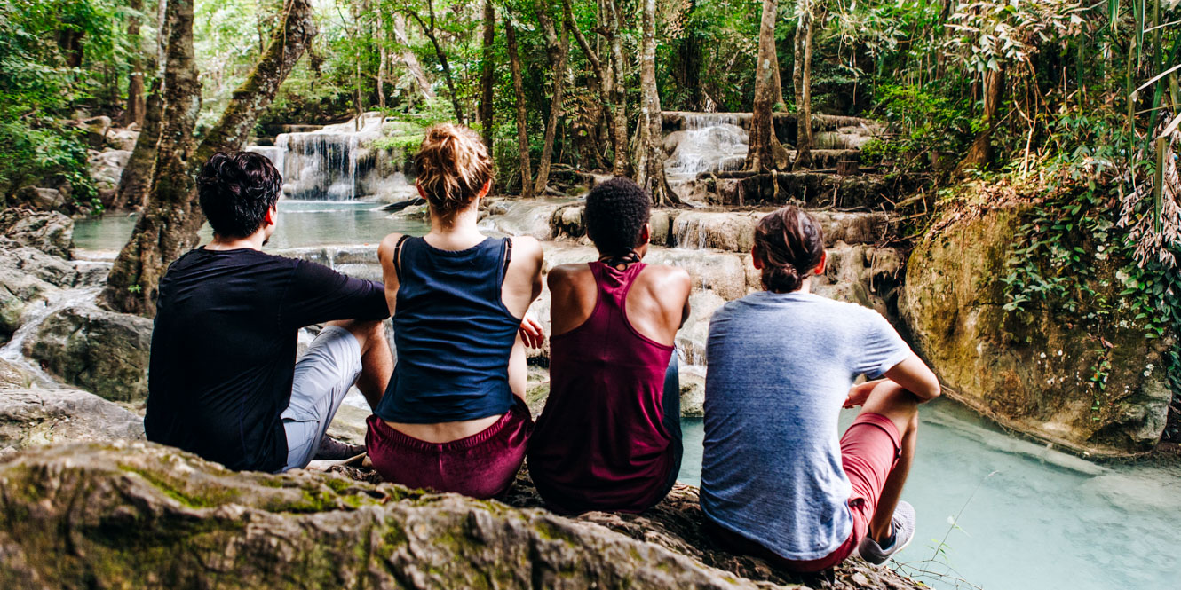Group of college students sit on rock by river