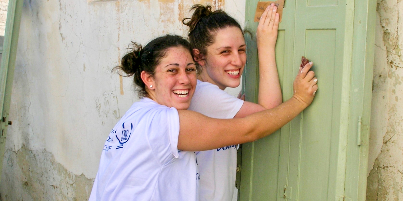 Smiling college students lean against door