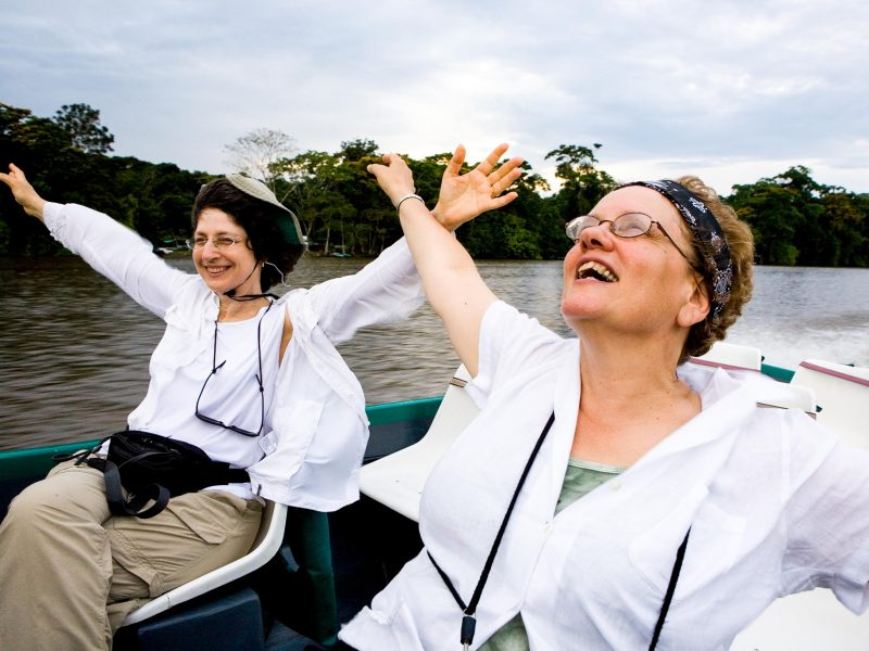 Women spread arms in joy on boat trip