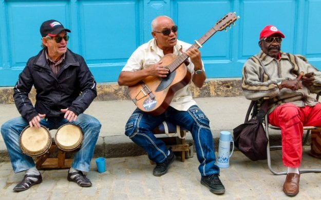Men play instruments on Cuba street curb