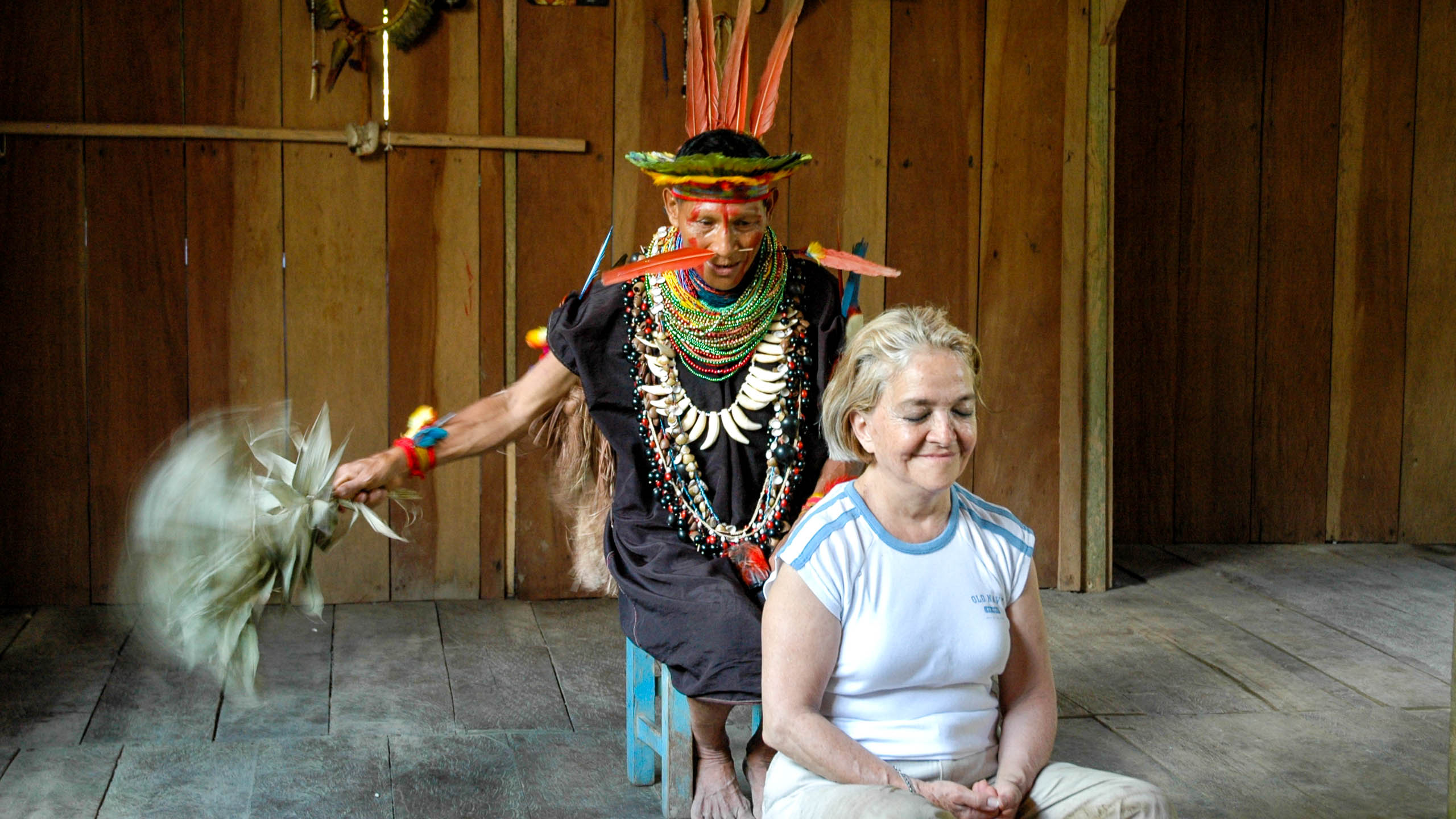 Woman sits in front of Ecuador man in traditional dress