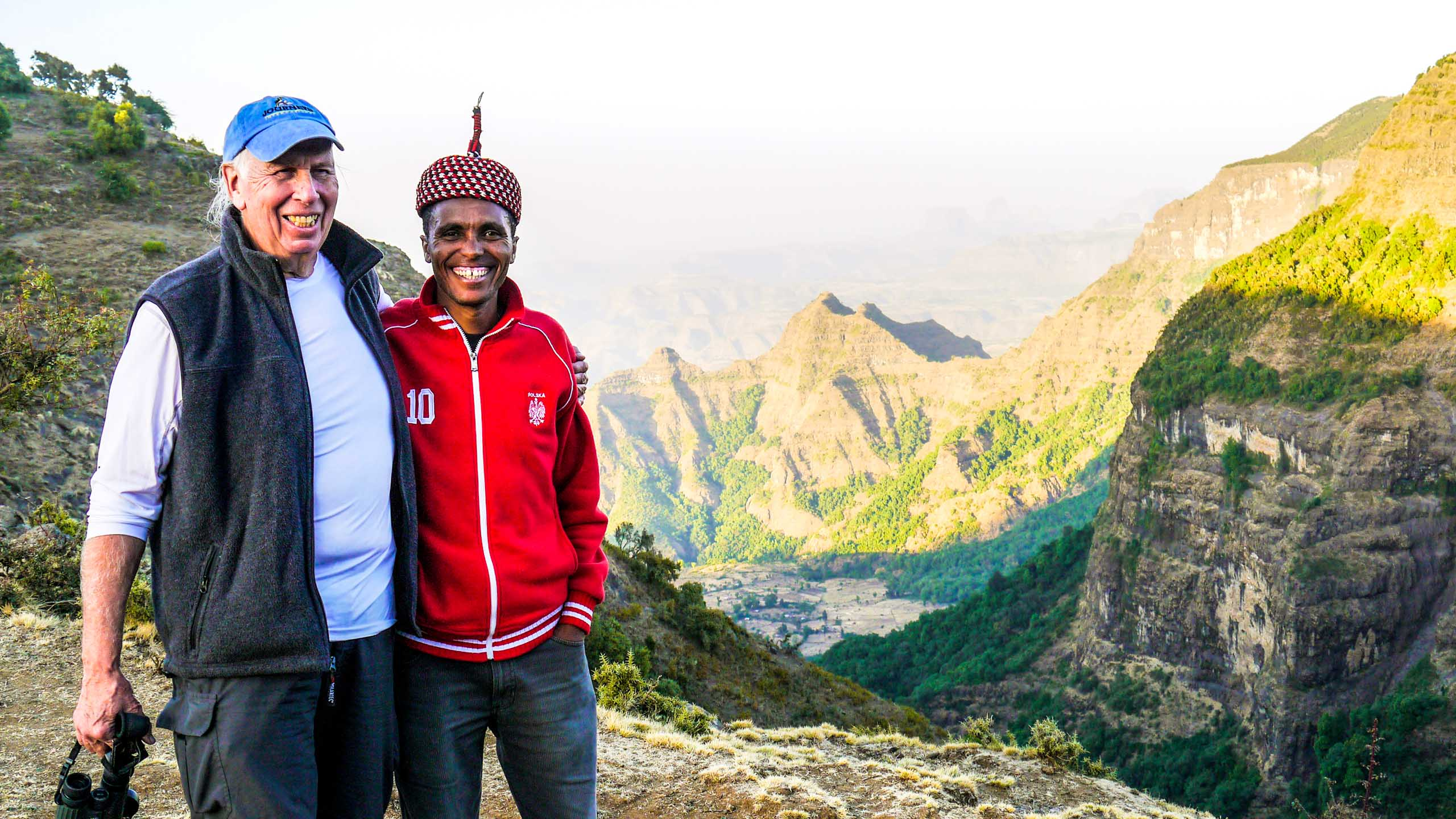 Two men pose in front of Ethiopia landscape