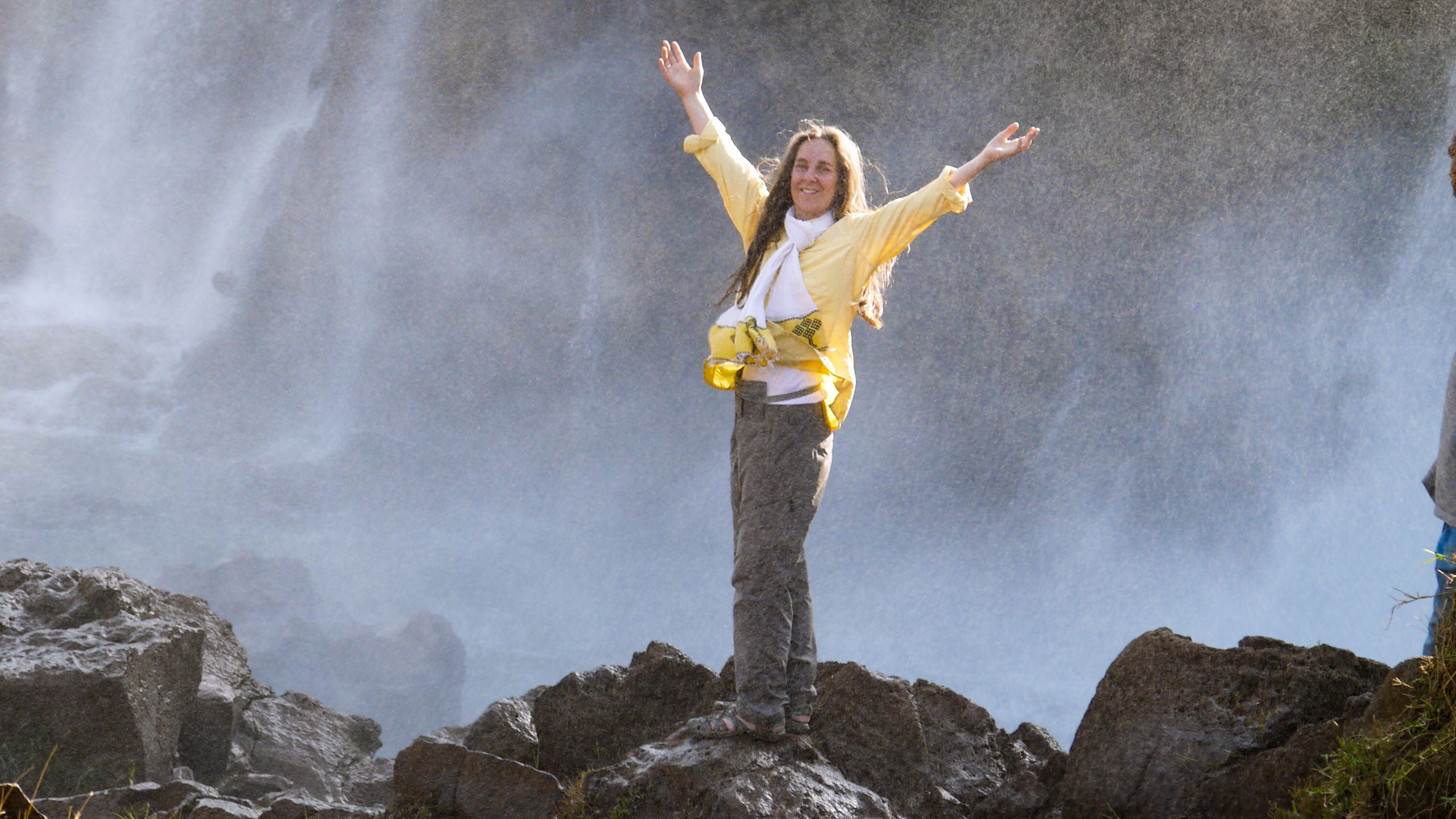Woman holds arms up in front of Ethiopia waterfall