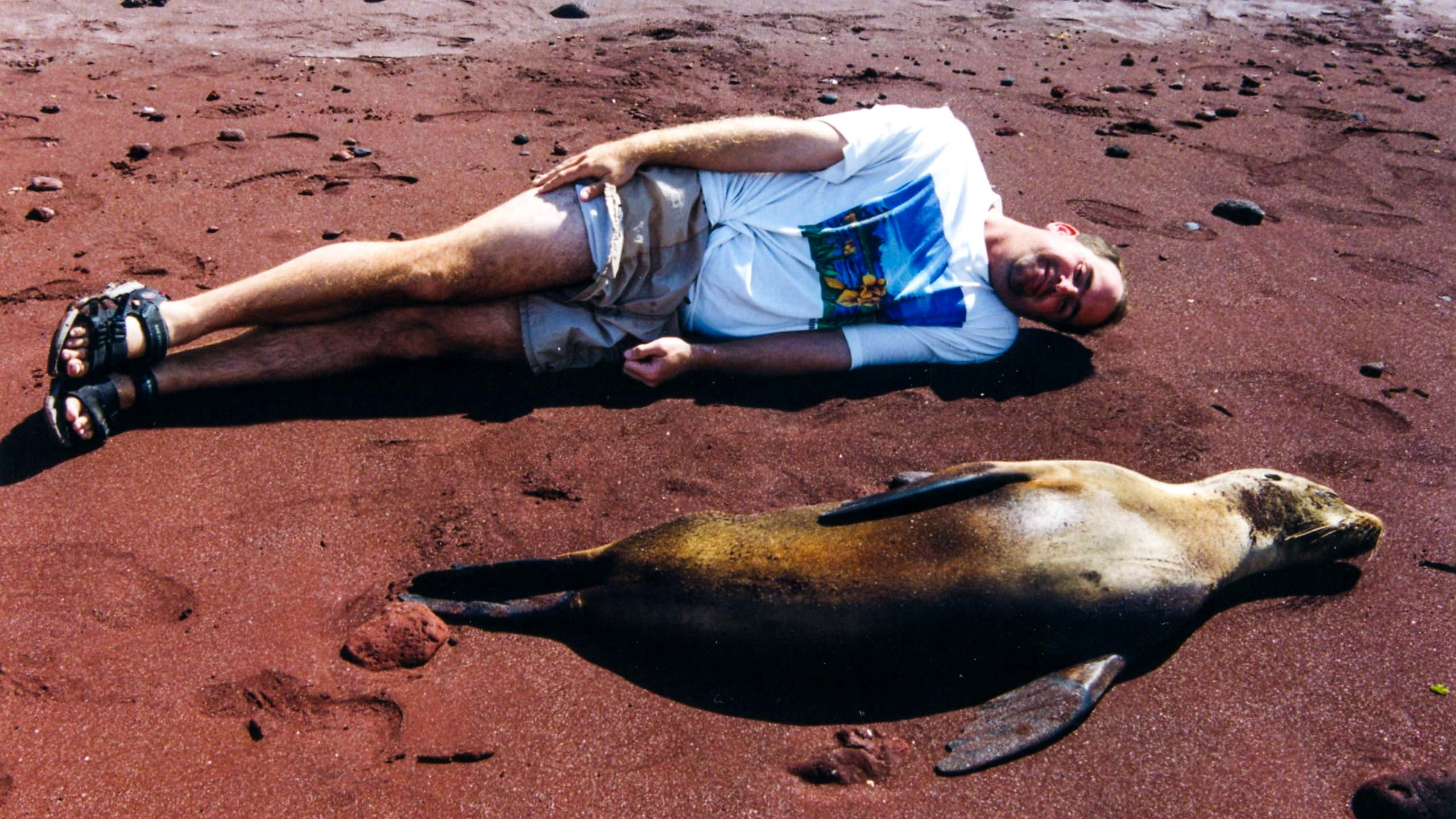 Traveler lies next to seal in Galapagos
