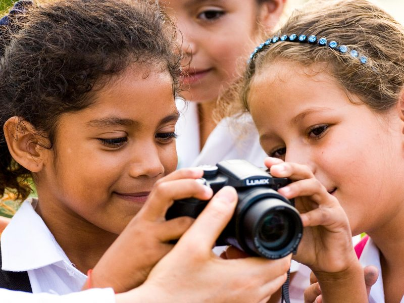 Young girls look at back of digital camera