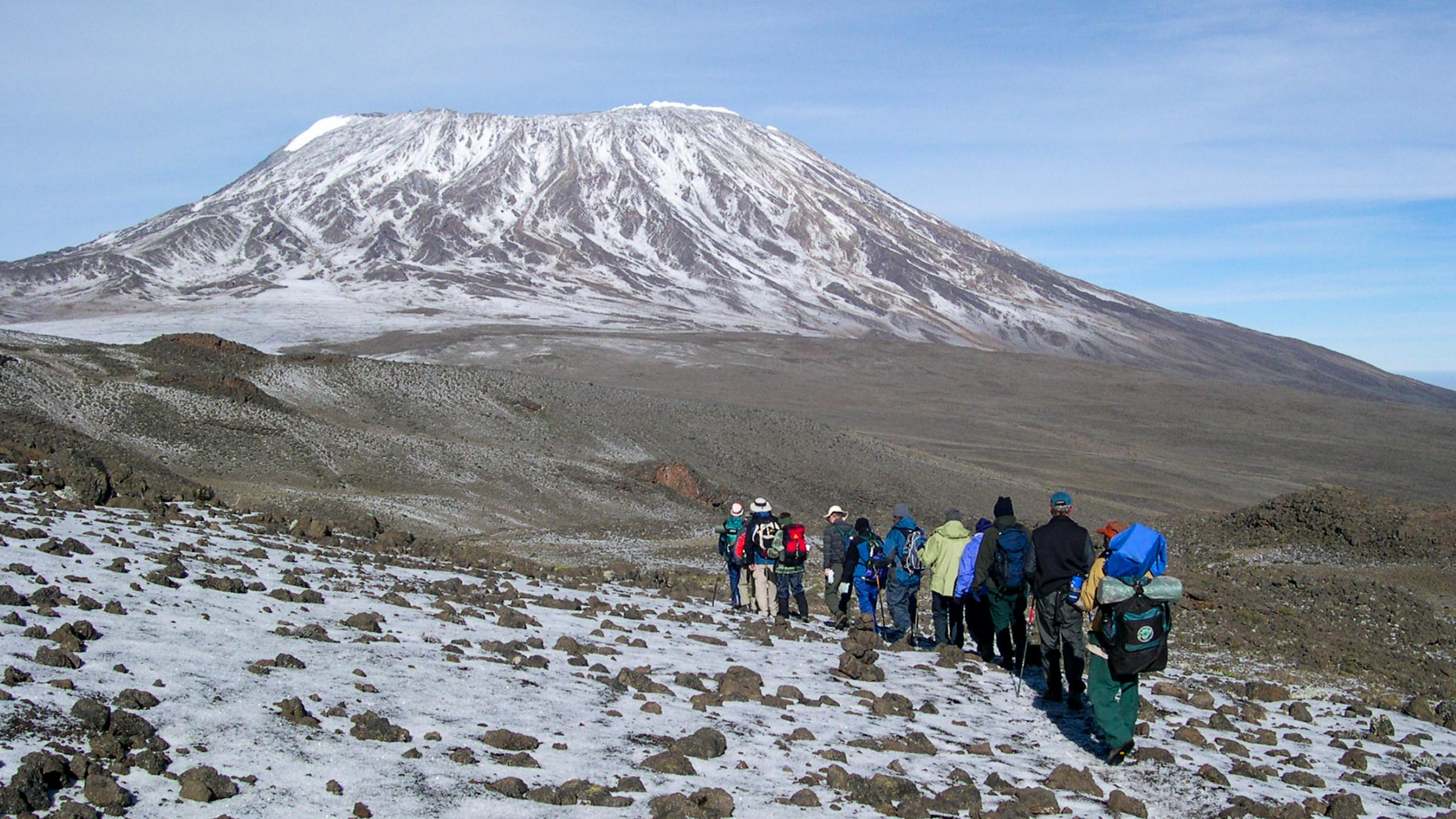 Group of travelers hike toward Mt Kilimanjaro