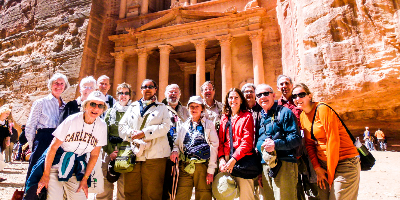 Group of travelers stands in front of Jordan cliff temple
