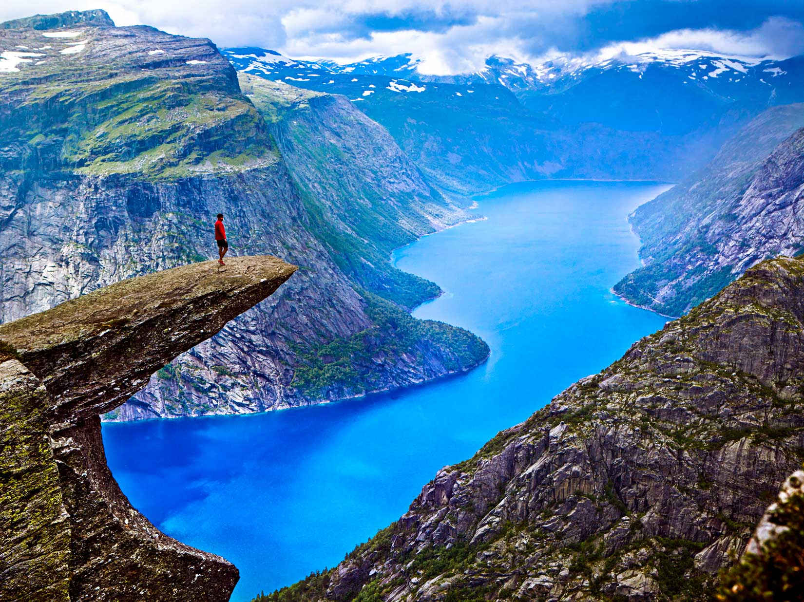 Hiker stands on rocky overlook in Norway