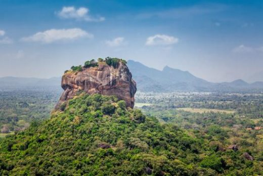 Spectacular view of the Sigiriya Lion rock surrounded by green rich vegetation. Picture taken from Pidurangala mountain in Dambula