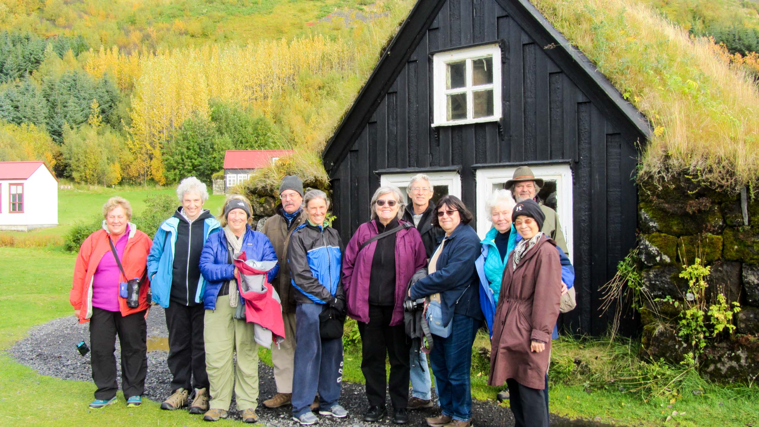 Group of travelers stands near Iceland cottage