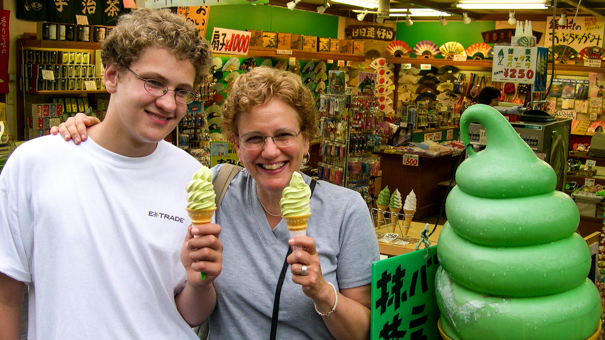 Teen boy and older woman hold ice cream cones