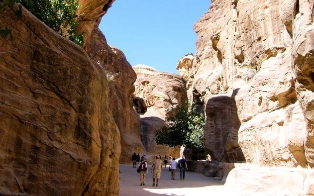 Travelers walk through valley between Jordan cliffs