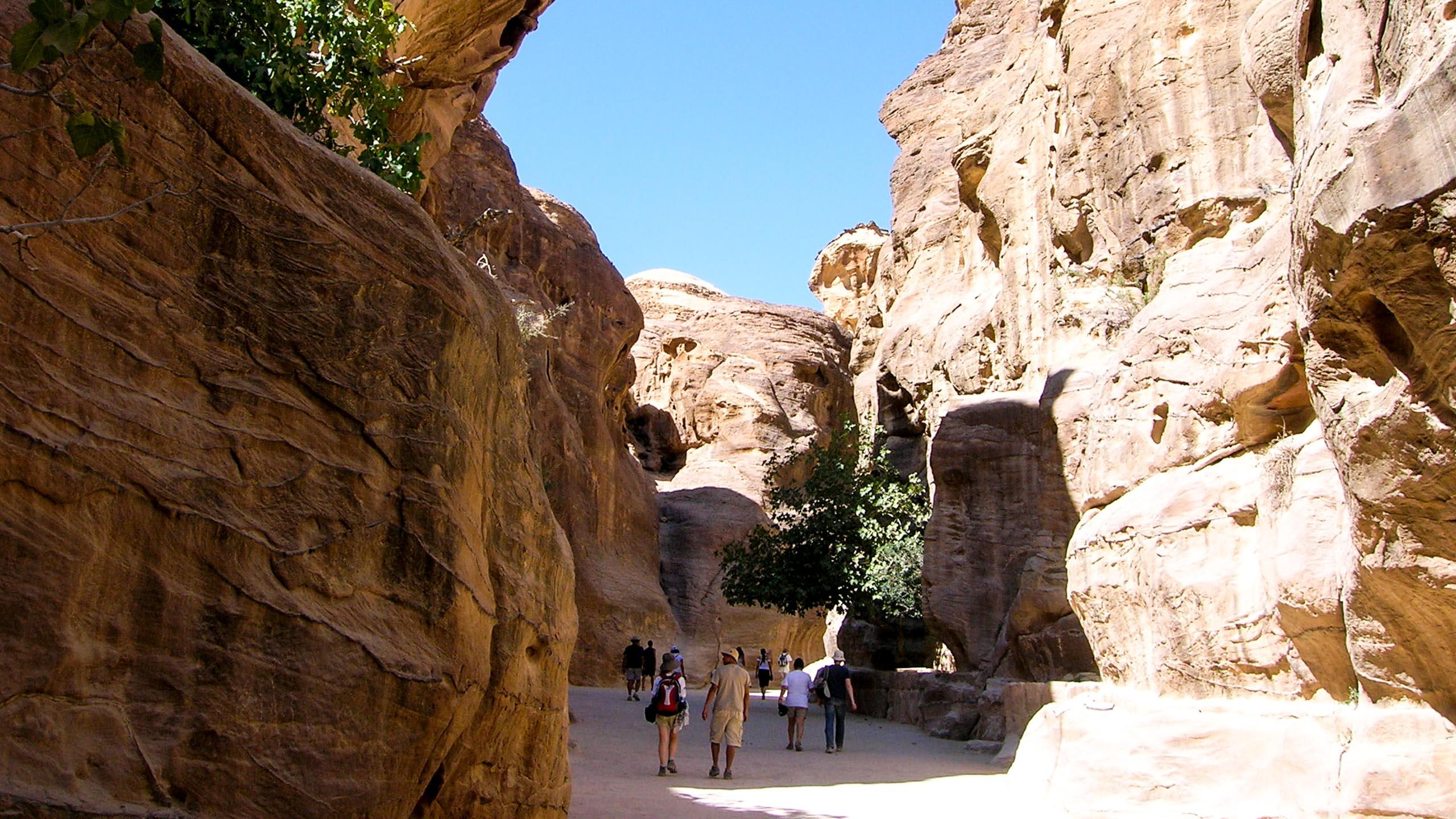 Travelers walk through valley between Jordan cliffs
