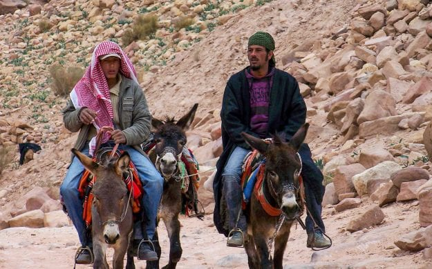 Two men ride on camels in Jordan desert