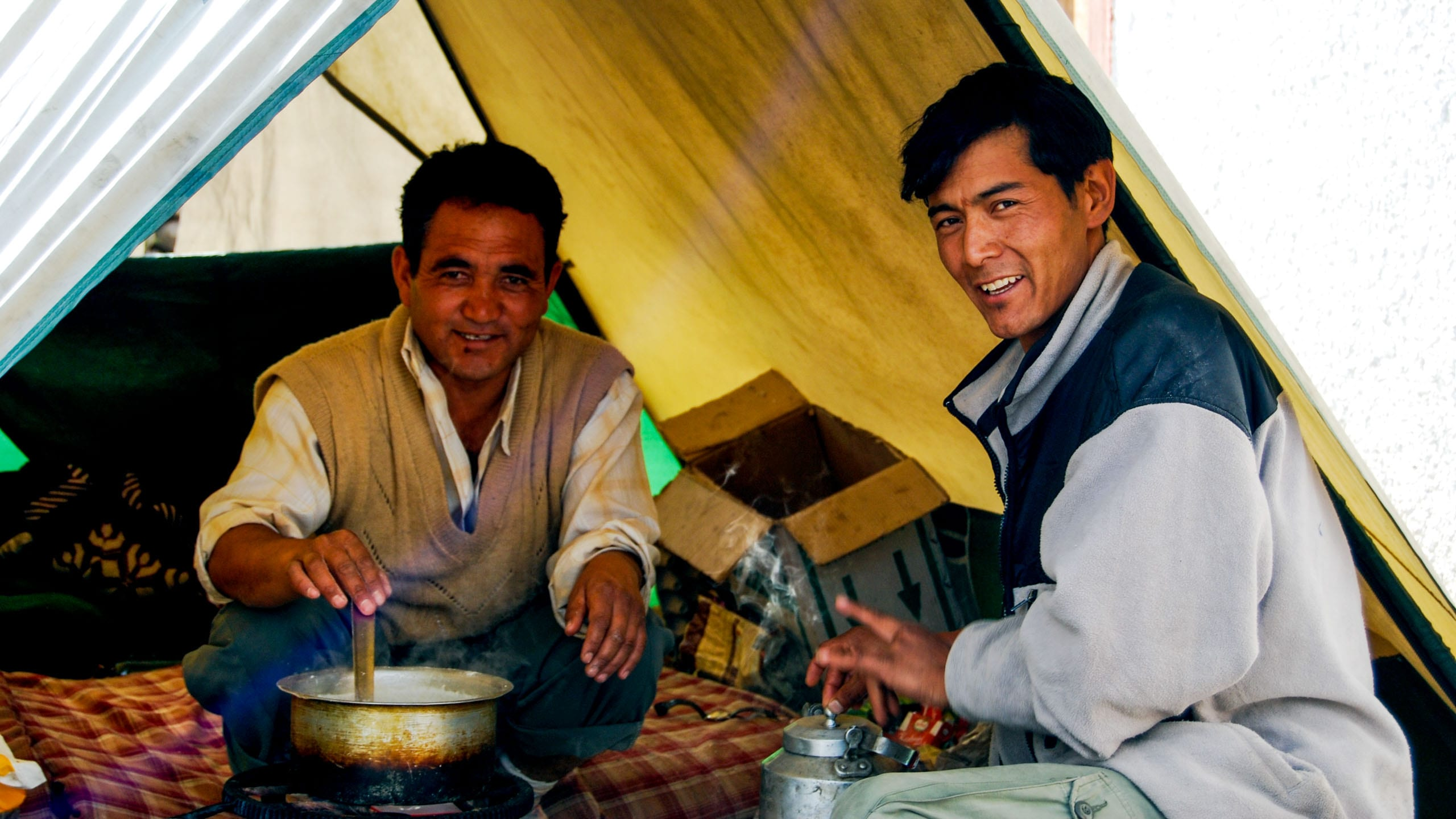 Two men sit to eat dinner in Ladakh tent