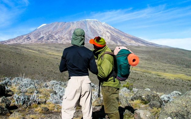 People look across Tanzania toward Mt Kilimanjaro