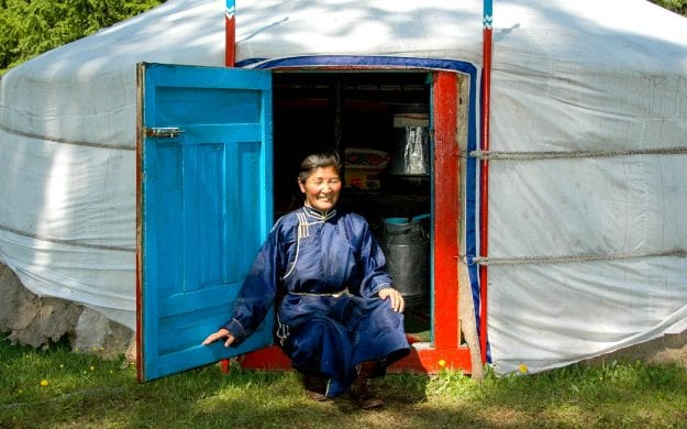 Mongolian person sits in front of ger