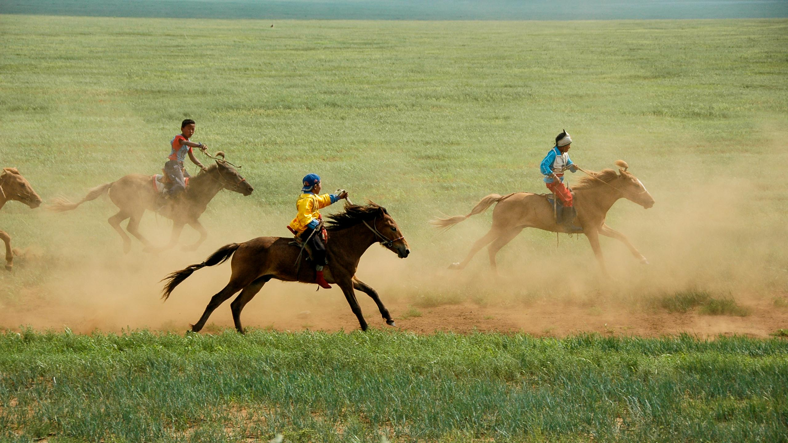 Mongolian people ride horses across plains
