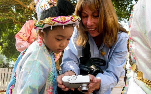 Woman shares digital photos with Myanmar child