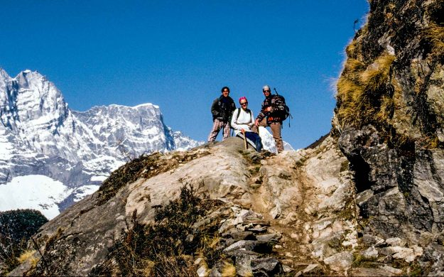 Everest hiking group rests on rock outcrop