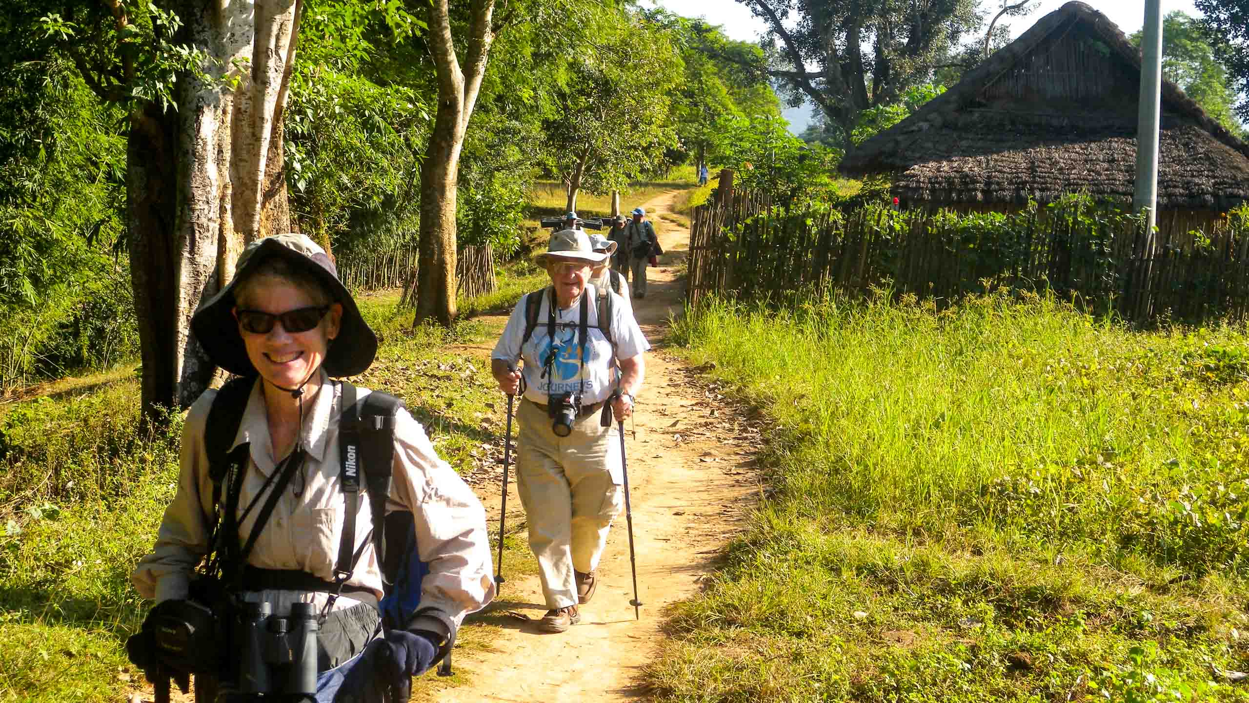 Travel group hikes through Nepal field