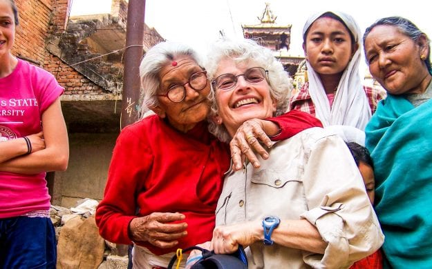 Nepal woman hugs smiling traveler