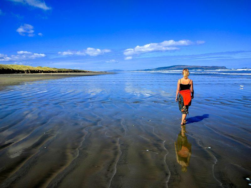 Woman walks along New Zealand beach