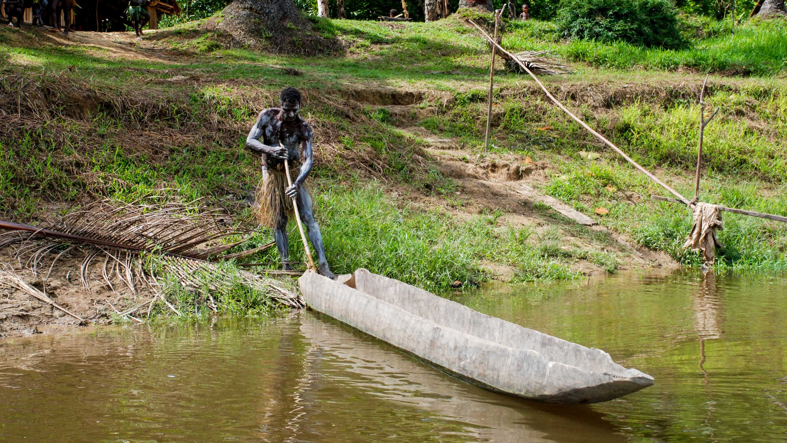 Papua New Guinea man pushes boat into river