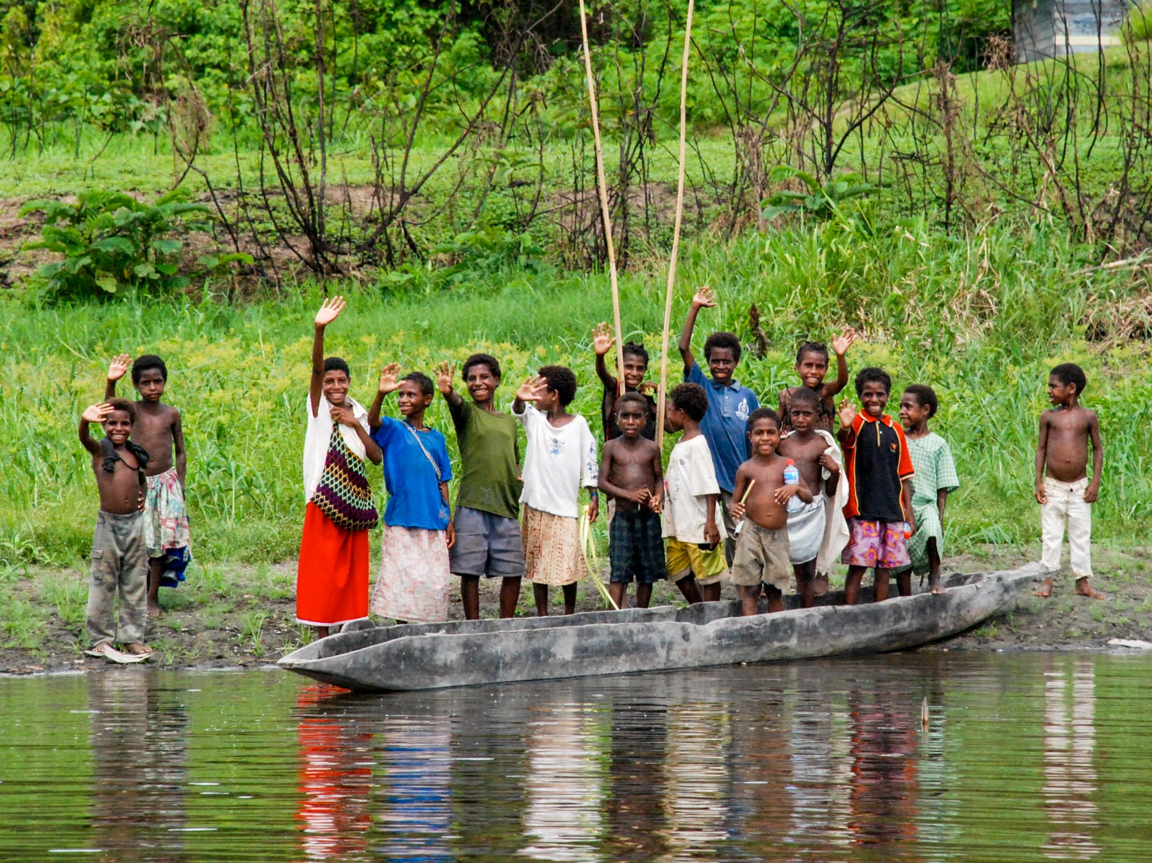 Group of children waves from the bank of a river