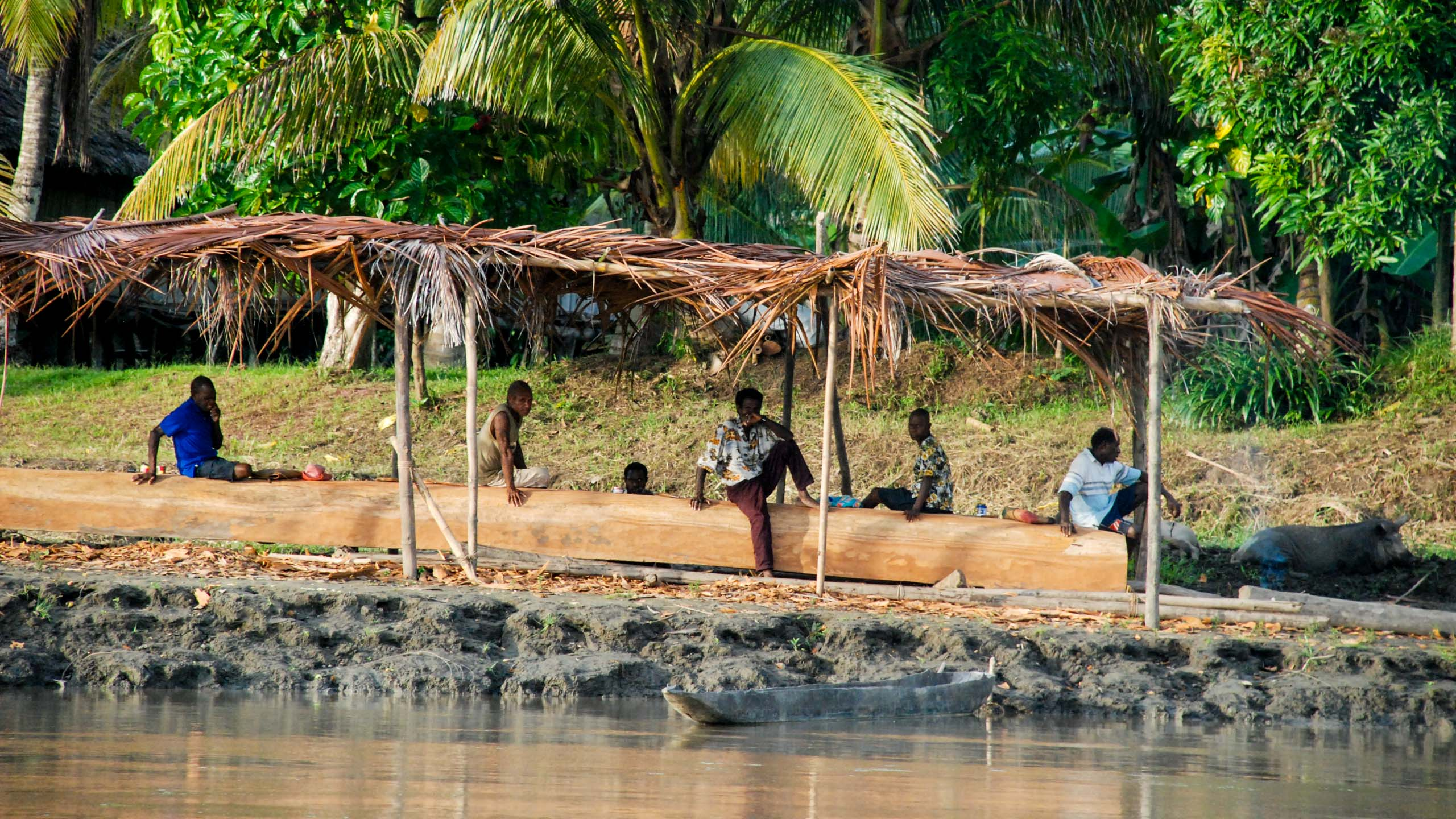 Papua New Guinea people sit on shore