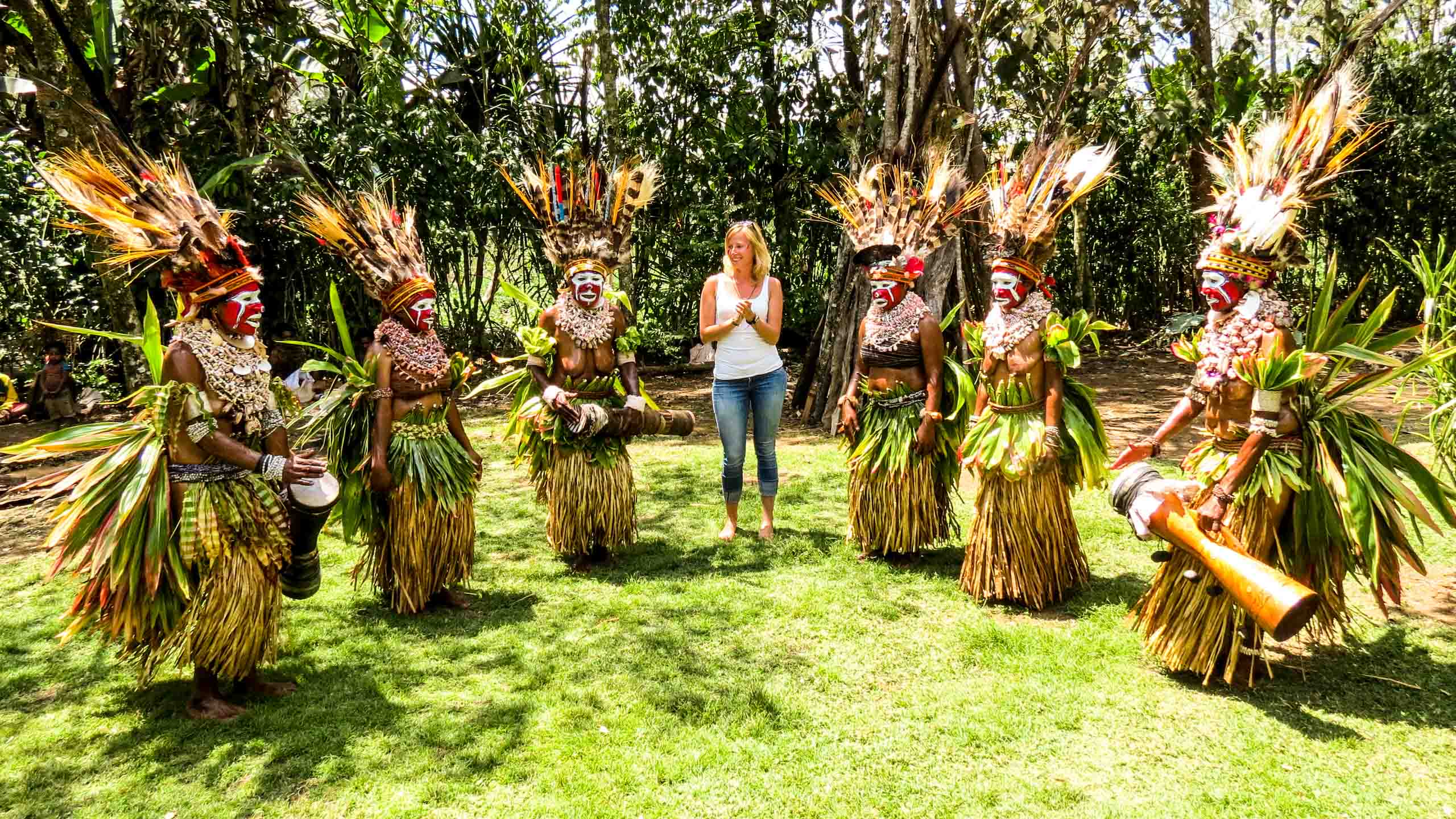 Traveler stands with group of Papua New Guinea natives