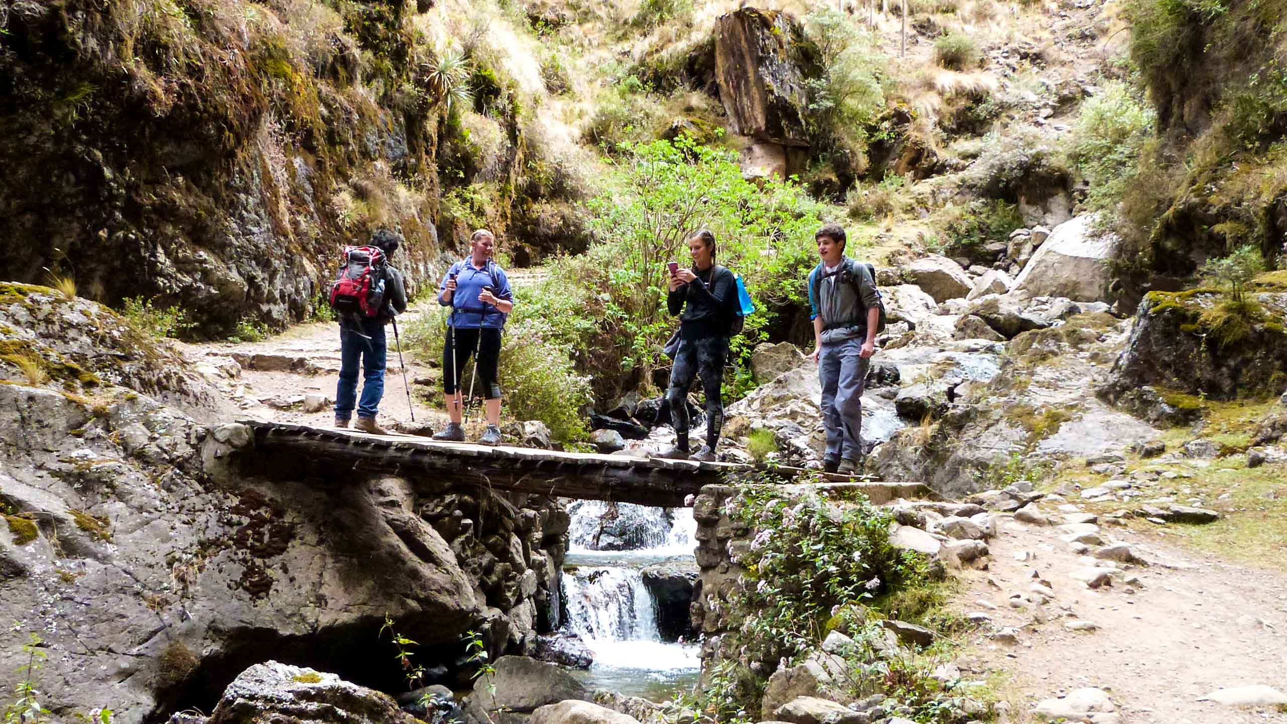 Travel group hikes across stream in Peru