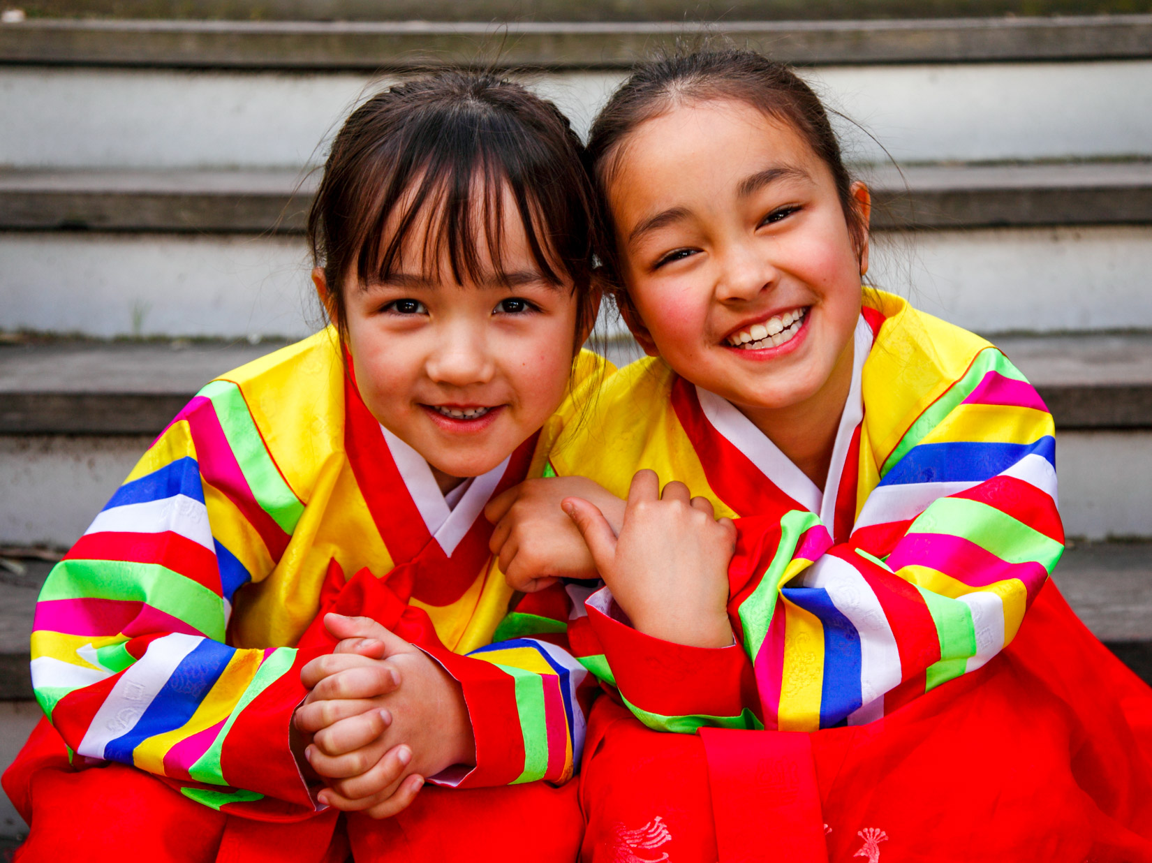Two young girls in colorful hanboks smile brightly