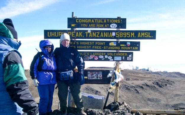 Hikers stand at top of Mt Kilimanjaro