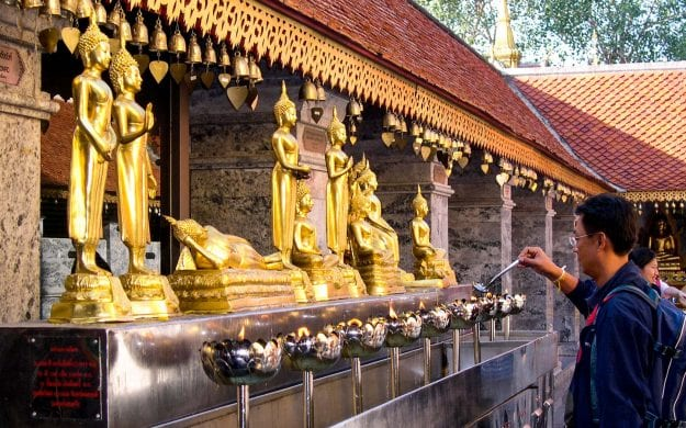 Thailand man lights candles at temple