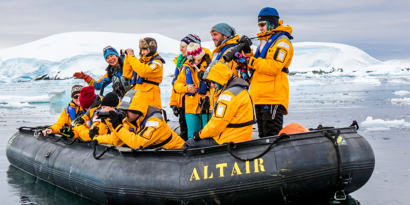 Tour group takes photo from raft in Antarctica