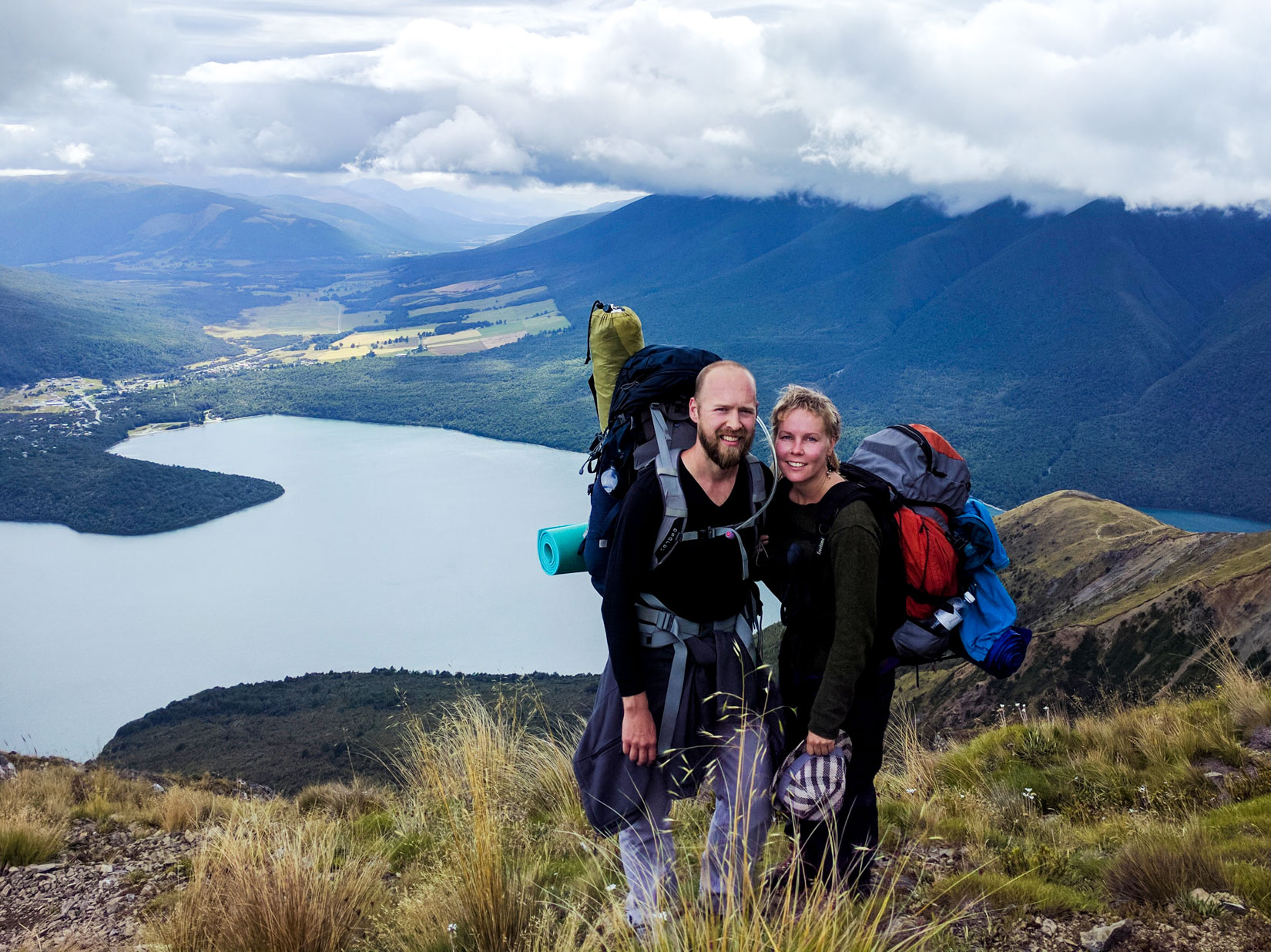 Two hikers stand in front of New Zealand lake