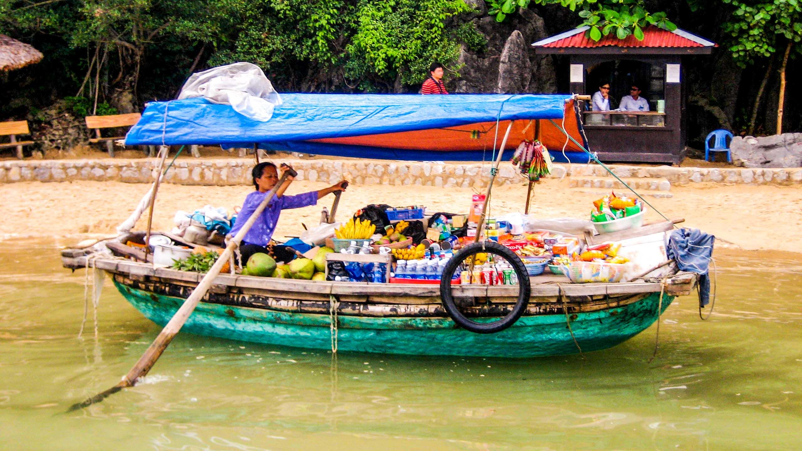 Woman rows boat full of goods in Vietnam